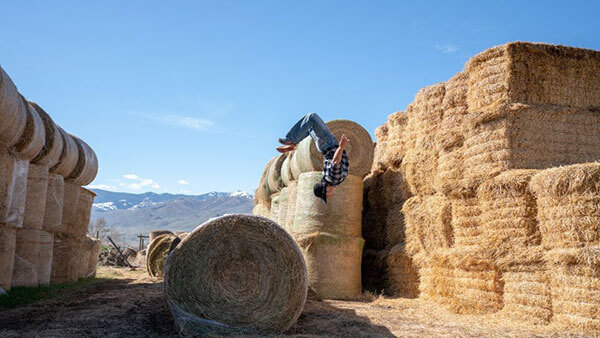 Lance Pekus doing a flip off of hay bales on his ranch